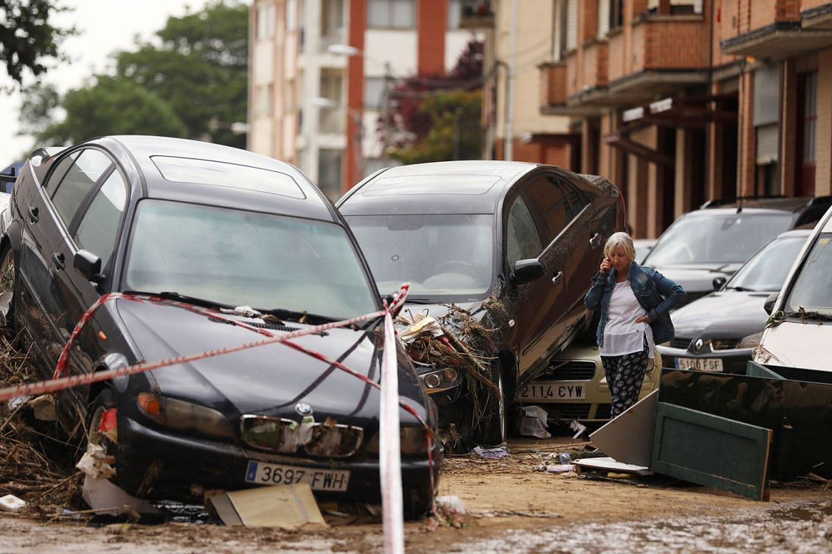 A woman speaks on the phone next to damaged cars after heavy rainfall in Tafalla, Spain, July 9, 2019. PHOTO: REUTERS