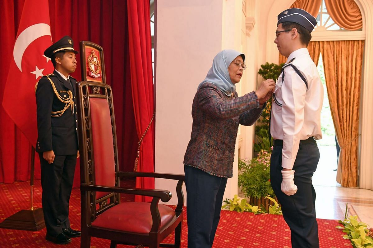 Senior Cadet Lieutenant Jason Timothy Pan, 18, receiving the President's Award, the highest accolade in Singapore Boys' Brigade Programme, from President Halimah Yacob at the Istana on July 9, 2019. PHOTO: THE STRAITS TIMES/DESMOND FOO
