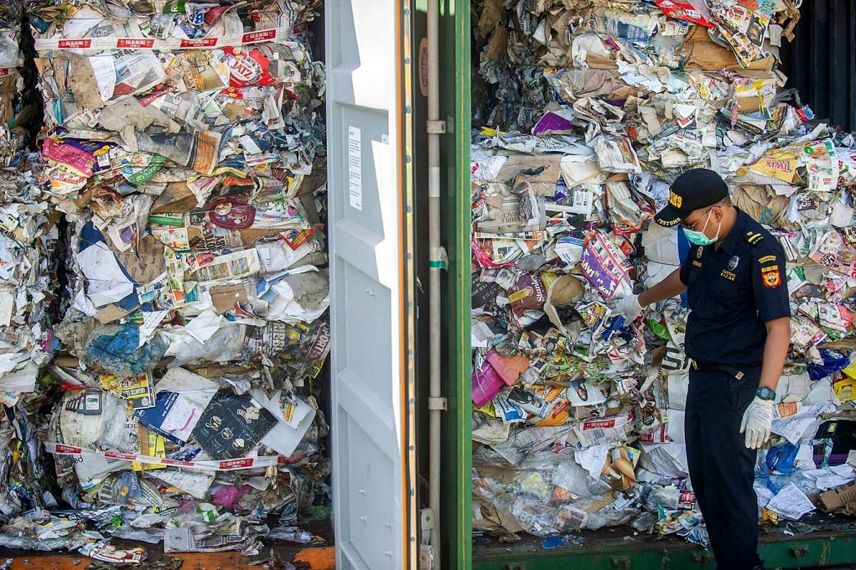 An Indonesian customs officer inspects containers filled with trash originating from Australia, which should have contained only waste paper, but authorities also found hazardous material and household trash, at a port in Surabaya on July 9, 2019. PH