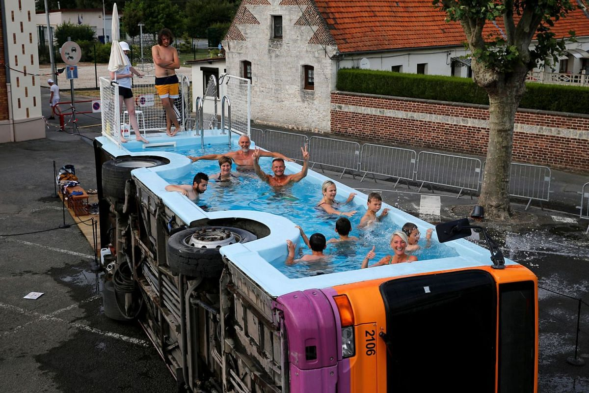"""People bathe in a decommissioned city bus named """"le bus piscine"""", an artwork by the French artist Benedetto Bufalino in Gosnay near Bethune, France, July 10, 2019. PHOTO: REUTERS"""