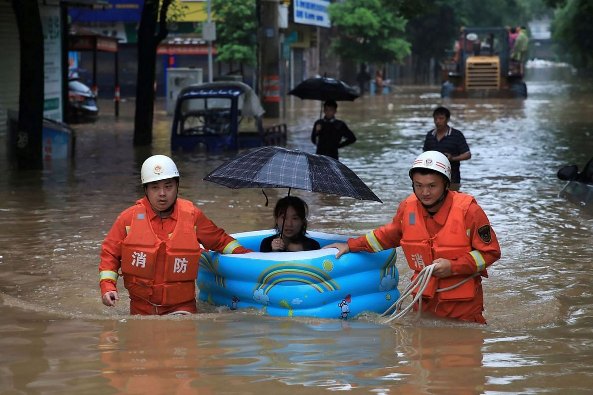 Rescue workers wade through flood waters as they evacuate a woman with an inflatable swimming pool on a street following heavy rainfall in Pingxiang, Jiangxi province, China on July 9, 2019. PHOTO: REUTERS