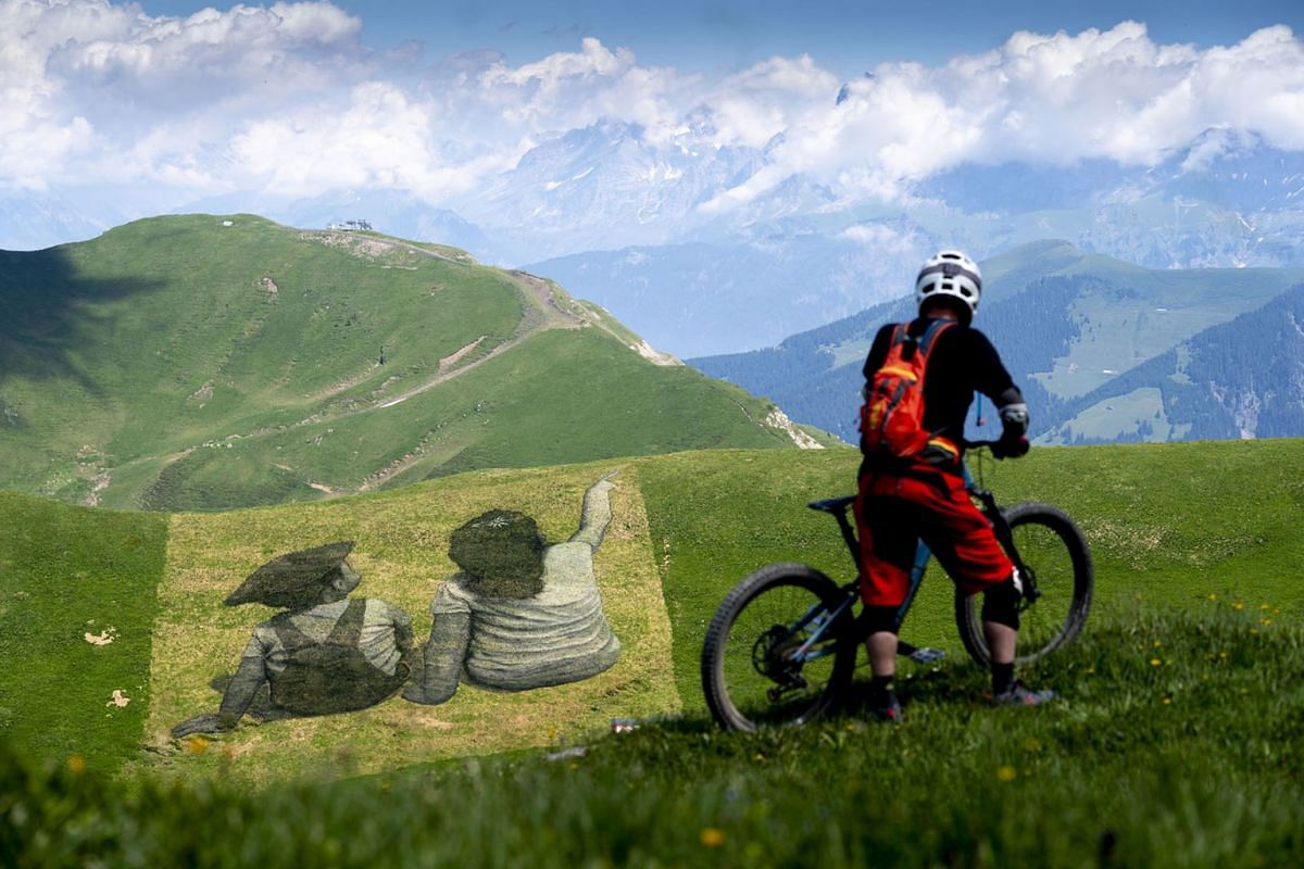 A mountain biker looking at a giant biodegradable landart painting by French-Swiss artist Saype, titled The Smugglers Of Friendship! (Les contrebandiers de l'amitie! in French) in the Swiss-French ski area Portes du soleil, in Les Crosets, Val d'Illi