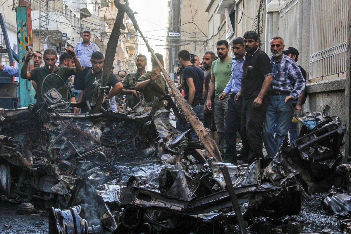 Syrian Kurdish security forces lift the wreckage of a rigged car which detonated outside the Syriac Orthodox Church of the Virgin Mary in the predominantly Christian neighbourhood of al-Wasti in the Kurdish-majority city of Qamishli in northeast Syri