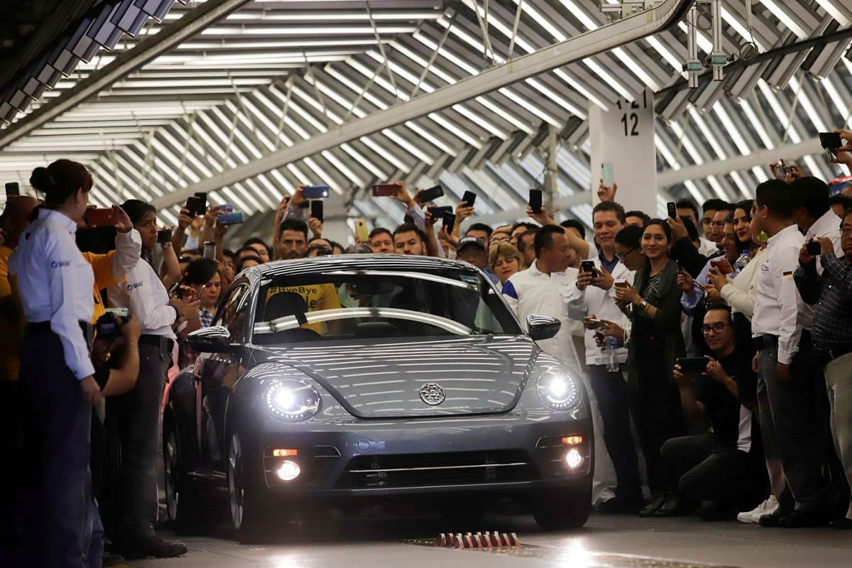 Employees take pictures of a Volkswagen Beetle car during a ceremony marking the end of production of VW Beetle cars, at company's assembly plant in Puebla, Mexico, July 10, 2019. PHOTO: REUTERS