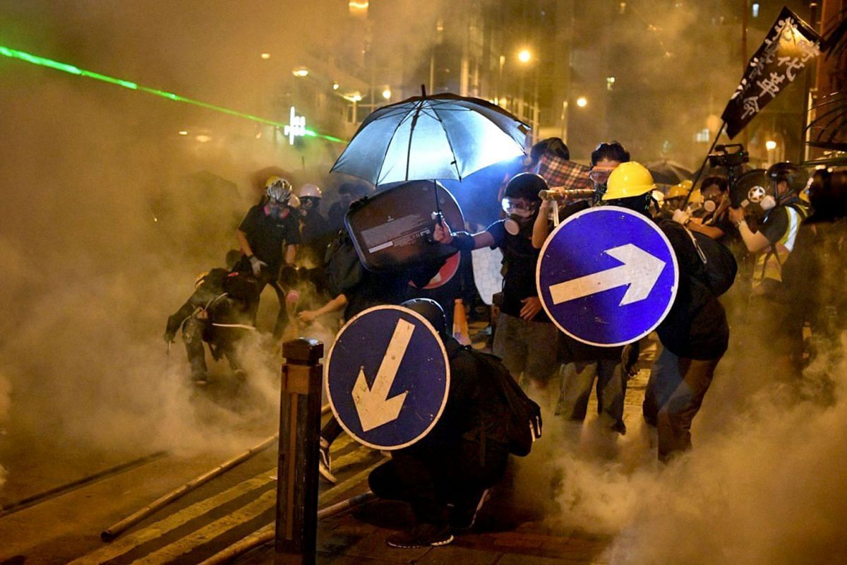 Hong Kong protesters defending themselves as tear gas envelops the streets on July 28, 2019.