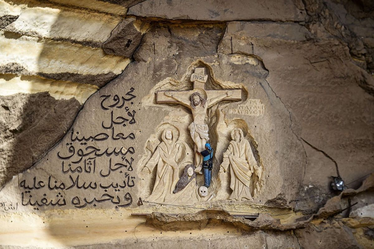 A photo issued on July 29, 2019 shows Polish artist Mario, sculptor of St Simon the Tanner Monastery complex, working on a scene relief depicting the crucifixion of Jesus Christ at the church in Egyptian capital Cairo's eastern hillside Mokattam dist