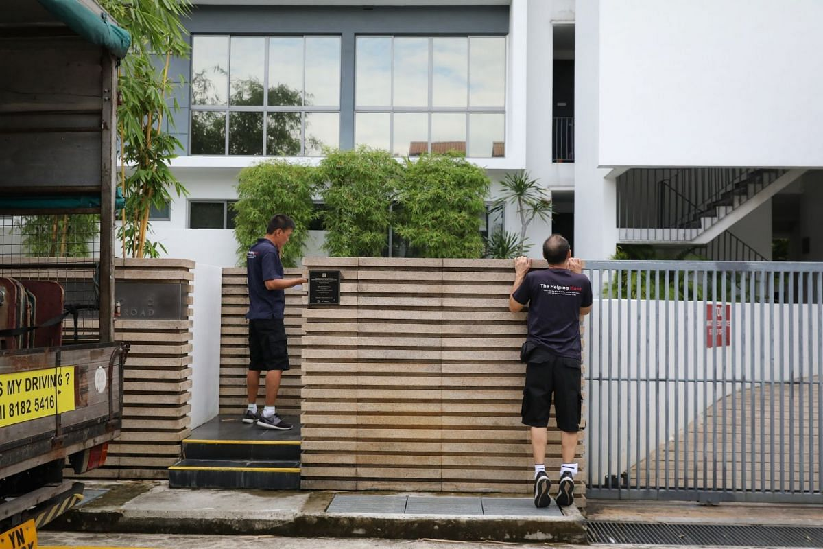The moving team arrives at a condominium. As the supervisor, Mr Kang (left) meets the client while fellow mover Pang Kok Chai, 57, surveys the surrounding area for a loading/unloading space.
