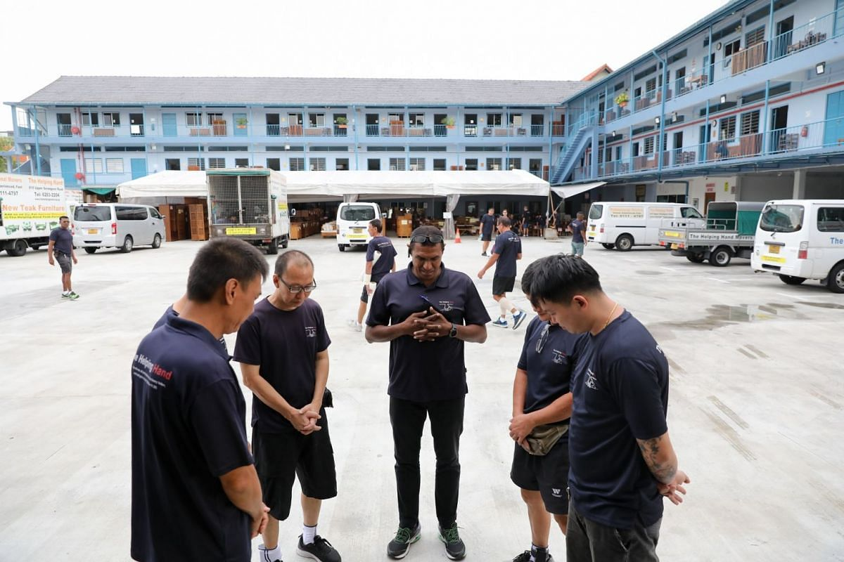 At 8.30am, before setting off, the team gathers for a prayer led by moving coordinator Sivabalan (centre), 49.