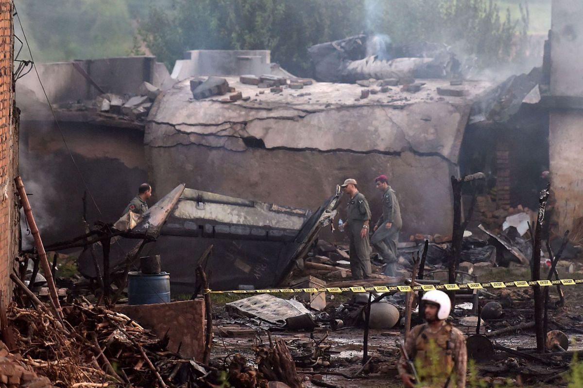 Pakistani soldiers cordon off the site where a Pakistani Army Aviation Corps aircraft crashed in Rawalpindi on July 30, 2019, killing fifteen people. PHOTO: AFP