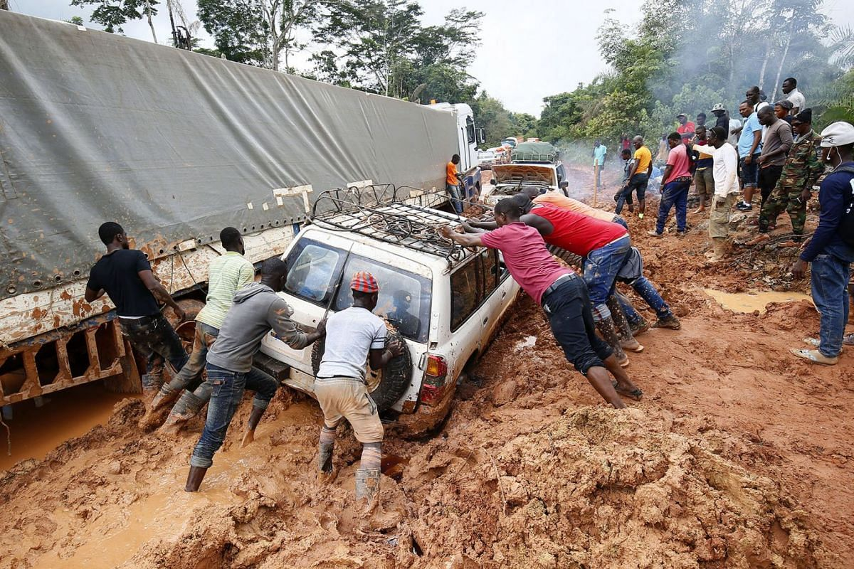Men push a vehicle on a muddy highway road in Nimba County, Liberia, 28 July 2019. PHOTO: EPA-EFE