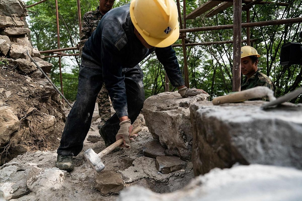 """Right: A worker at part of the Great Wall in Xiangshuihu in Huairou district on the outskirts of Beijing on May 17. This year, Beijing launched a national-level plan to """"guide restoration work"""", after criticism that shoddy work in the past had disfig"""