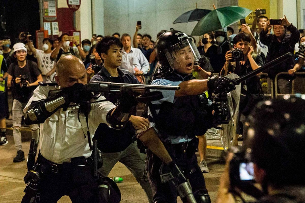 A police officer (left) points a firearm during clashes with protesters who had gathered outside Kwai Chung police station, in support of protesters detained with the charge of rioting, in Hong Kong on July 30, 2019. PHOTO: AFP