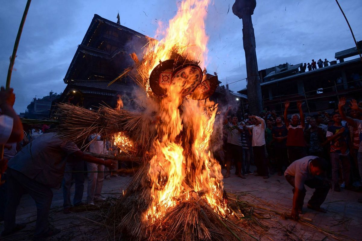 "Nepali devotees watch as a straw effigy of Ghanta Karna burns during celebrations of the Hindu festival of ""Gathemangal"", also known as Ghanta Karna, in Bhaktapur on the outskirts of Kathmandu on July 30, 2019. PHOTO: AFP"