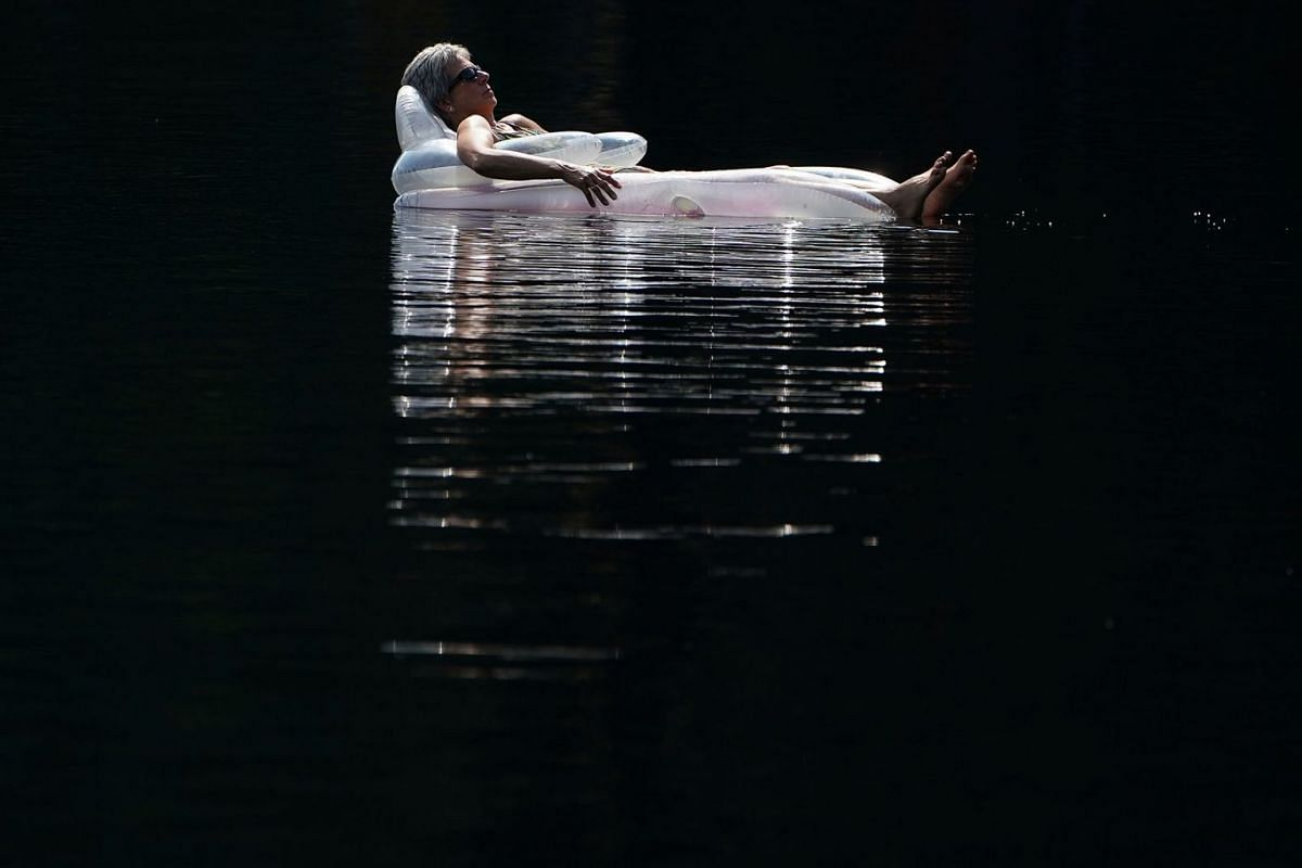 A woman floats on an air mattress in Mazinaw Lake at Bon Echo park in Cloyne, Canada, July 29, 2019. PHOTO: REUTERS