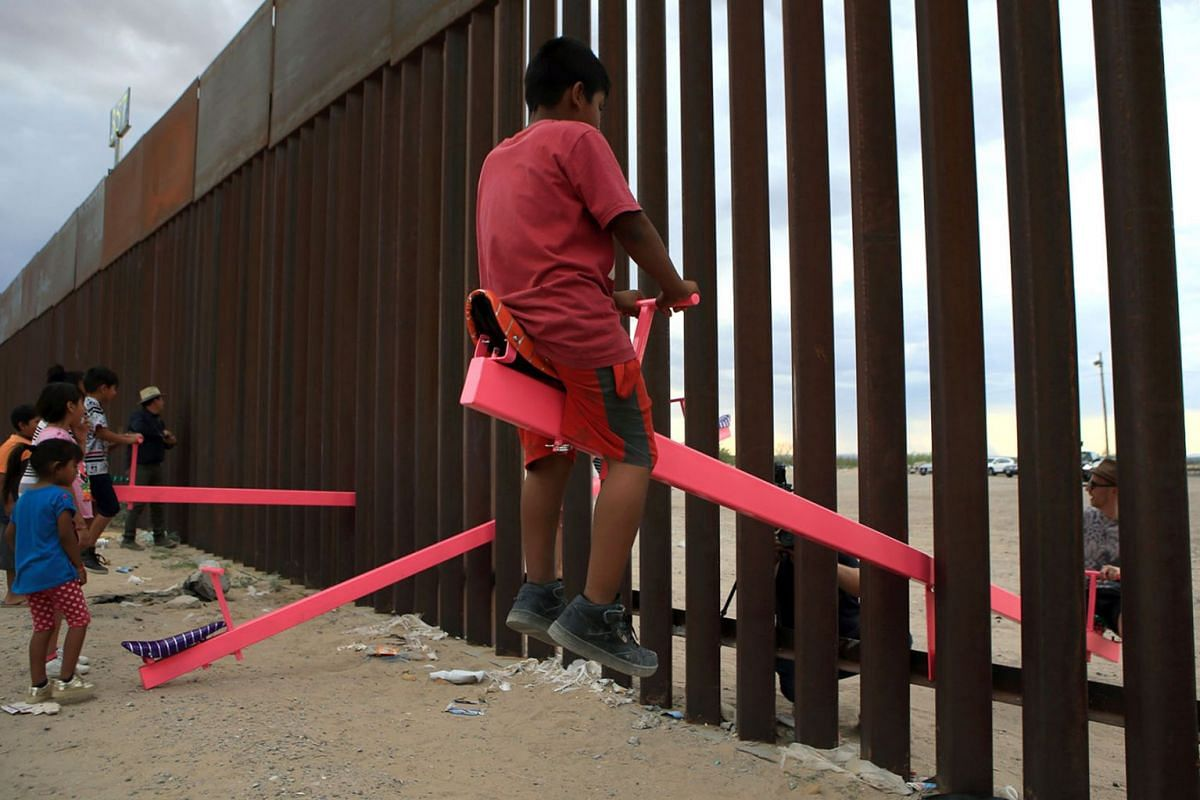 "American and Mexican families play with a toy called ""up and down"" (Seesaw swing) over the Mexican border with US at the Anapra zone in Ciudad Juarez, Chihuahua State, Mexico on July 28, 2019. PHOTO: AFP"