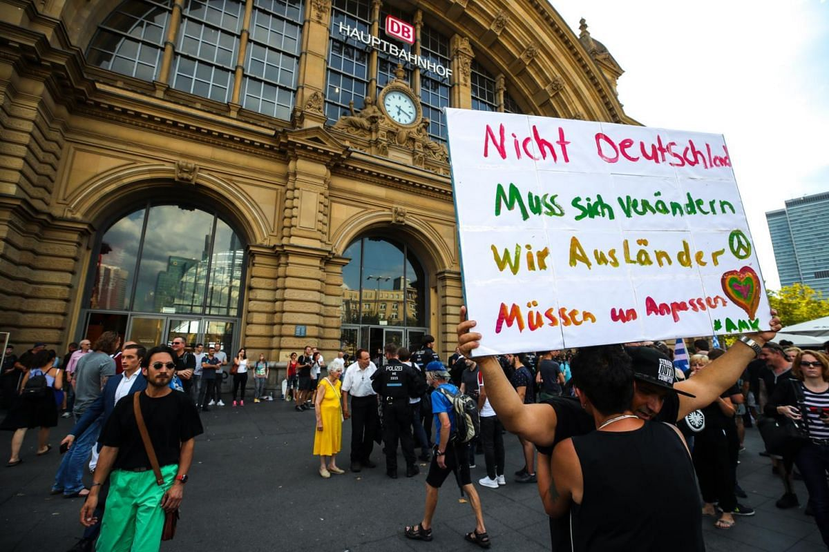 """A protester holding a banner that reads """"Not Germans have to change, we foreigners have to adapt"""" as people attend a memorial service in front of the main train station in Frankfurt on July 30, 2019."""
