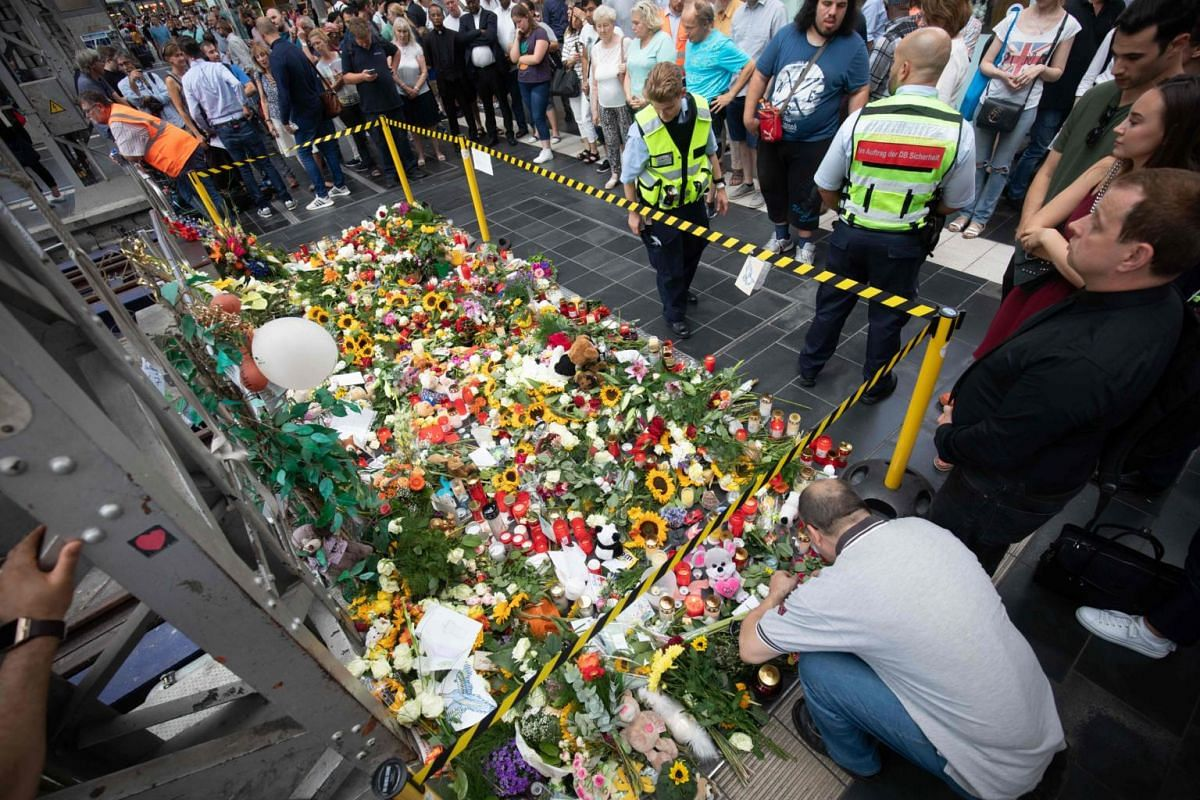 People placed flowers, toys and candles near the place where the child was pushed onto the tracks in Frankfurt's central station, on July 30, 2019.