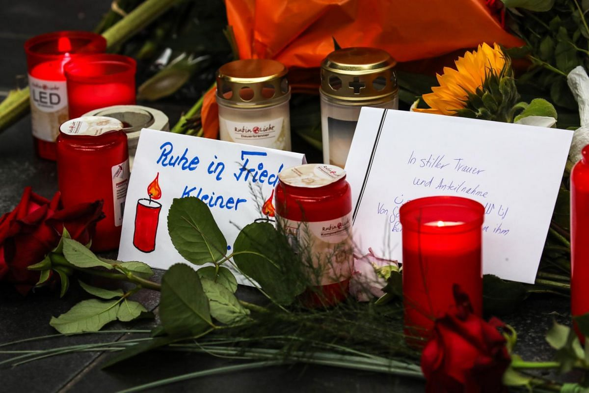 People put flowers and candles near the place where a child was pushed onto the tracks in Frankfurt's central station (Hauptbahnhof), Germany, on July 30, 2019.