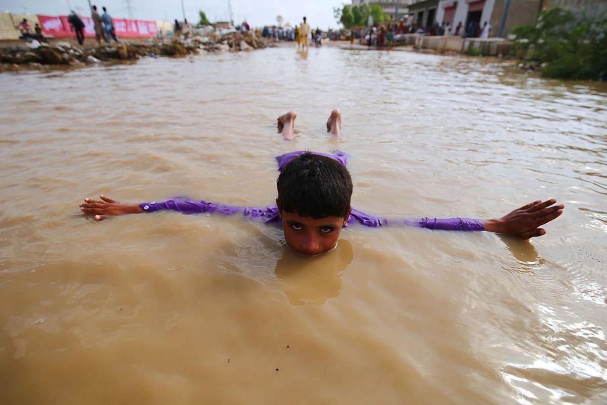 A boy plays in rain water after heavy monsoon rains in Karachi, Pakistan, 31 July 2019. PHOTO: EPA-EFE