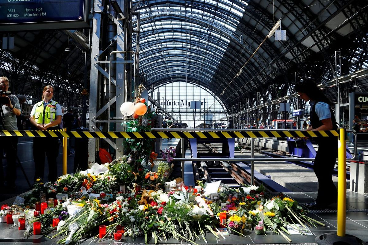 Messages of mourning, candles and flowers are placed by people for an eight-year-old boy who was pushed by a man in front of an oncoming train and died at the main train station in Frankfurt, Germany, July 30, 2019. PHOTO: REUTERS