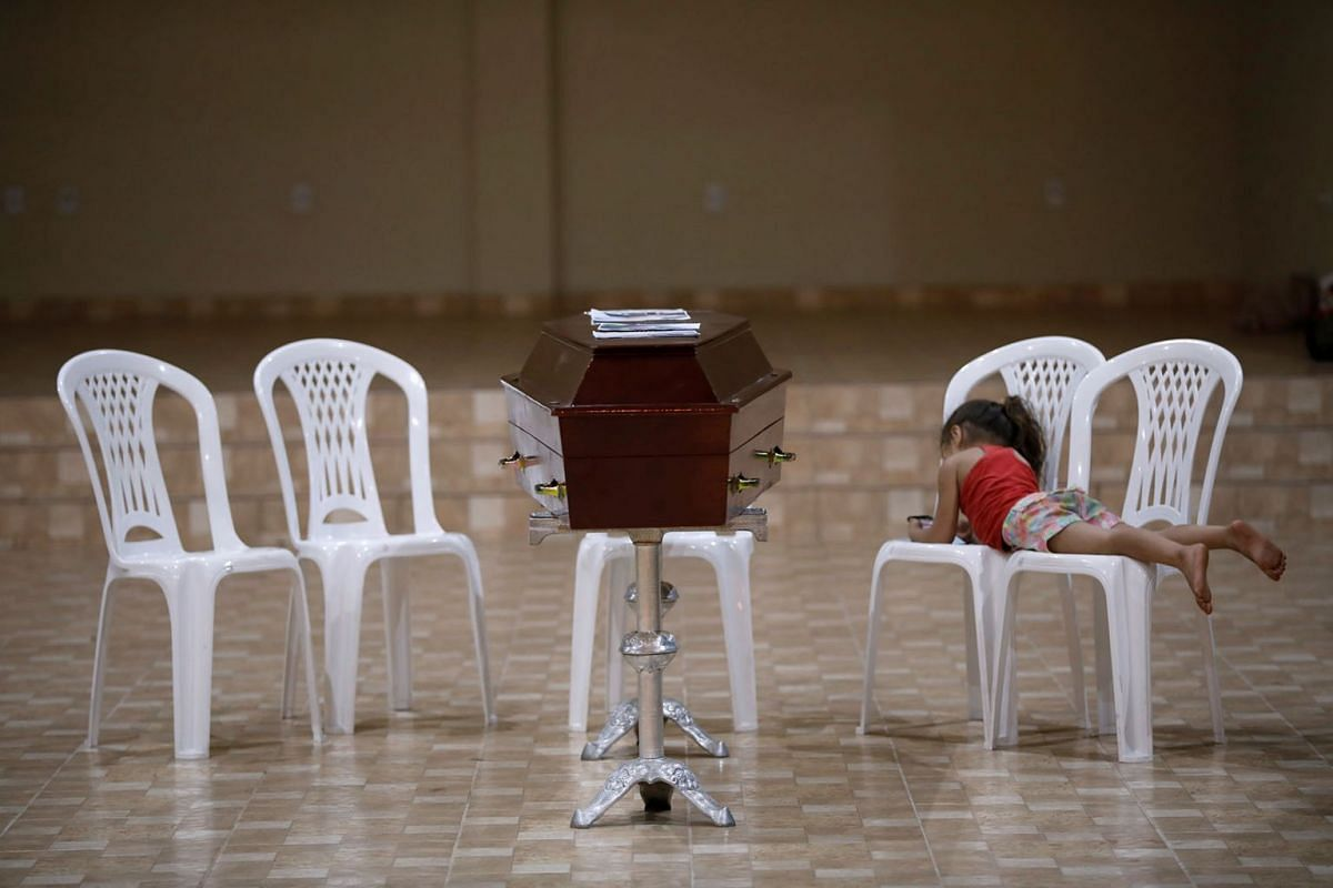 A relative of murdered prisoner, lies on a chair next to his coffin during a wake after a prison riot in the city of Altamira, Para state, Brazil July 30, 2019. PHOTO: REUTERS
