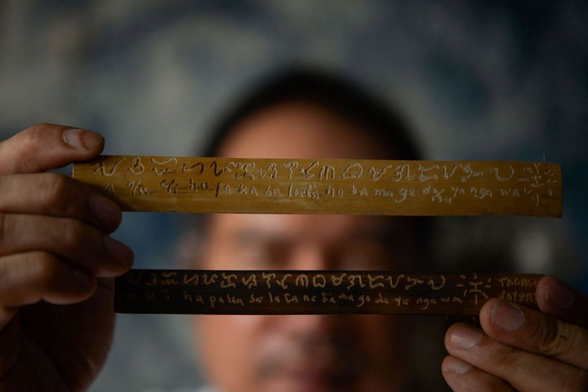 A photo issued on July 31, 2019 shows cultural advocate Leo Emmanuel Castro holding pieces of bamboo inscribed with indigenous Baybayin script at his shop in Manila, June 11, 2019. PHOTO: AFP