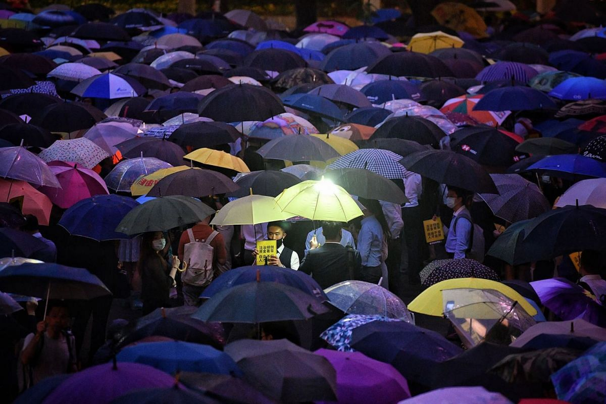 Hong Kong finance employees held umbrellas and staged a 'flash mob' protest at Chater Garden in the Central district of Hong Kong, China, on August 1, 2019. PHOTO: THE STRAITS TIMES/CHONG JUN LIANG