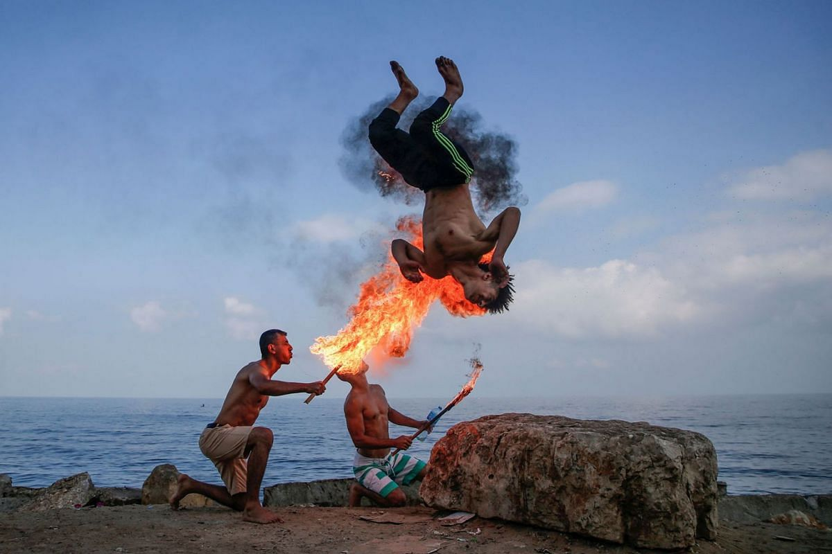 Palestinian men perform fire breathing on the beach as an entertainment for children during the summer vacation in Gaza City on August 1, 2019. PHOTO: AFP