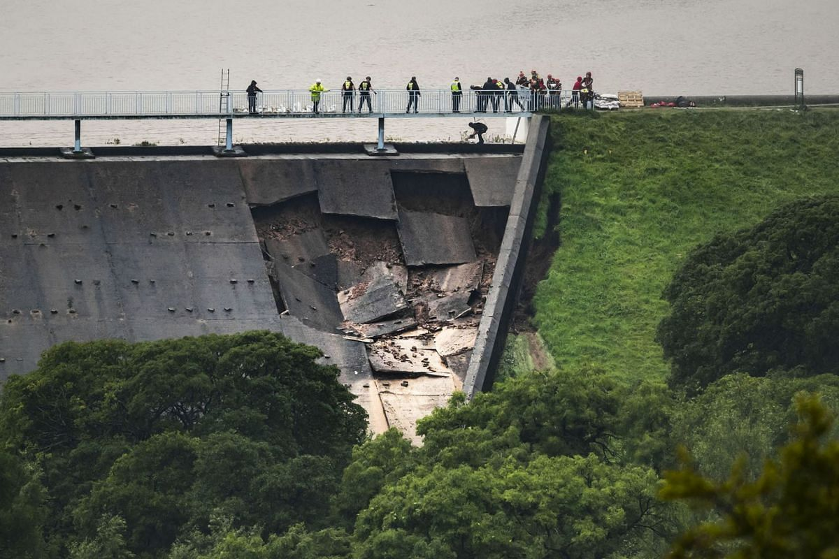 People human chain to lay sandbags on Toddbrook Reservoir near the village of Whaley Bridge, Cheshire, England, Thursday, Aug. 1, 2019. British police have ordered the evacuation of a town of 6,500 residents in northwest England over fears that a dam
