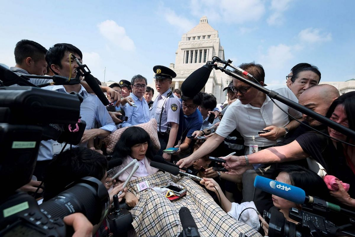 Wheelchair-bound Japanese lawmaker Eiko Kimura (C) is surrounded by the media upon her arrival at Parliament in Tokyo on August 1, 2019. PHOTO: AFP