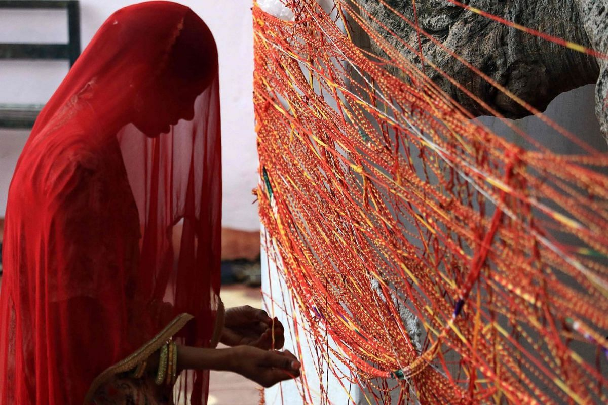 """A Hindu woman offers prayers as she ties a sacred thread to a """"Kalpavriksha"""" -- a divine wishing tree -- on the occasion of Hariyali Amavasya at an Hindu temple in Ajmer in the Indian state of Rajasthan on August 1, 2019.  PHOTO: AFP"""