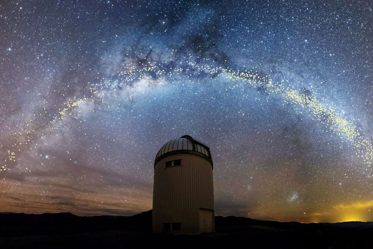 The warped shape of the stellar disk of the Milky Way galaxy, determined by mapping the distribution of young stars called Cepheids with distances set out in light years, is seen over the Warsaw University Telescope at Las Campanas Observatory in Chi