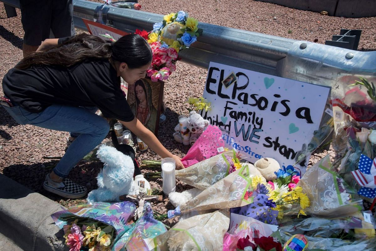 A woman places flowers beside a makeshift memorial outside the Cielo Vista Mall Wal-Mart (background) where a shooting left 20 people dead in El Paso, Texas, on August 4, 2019. PHOTO: AFP