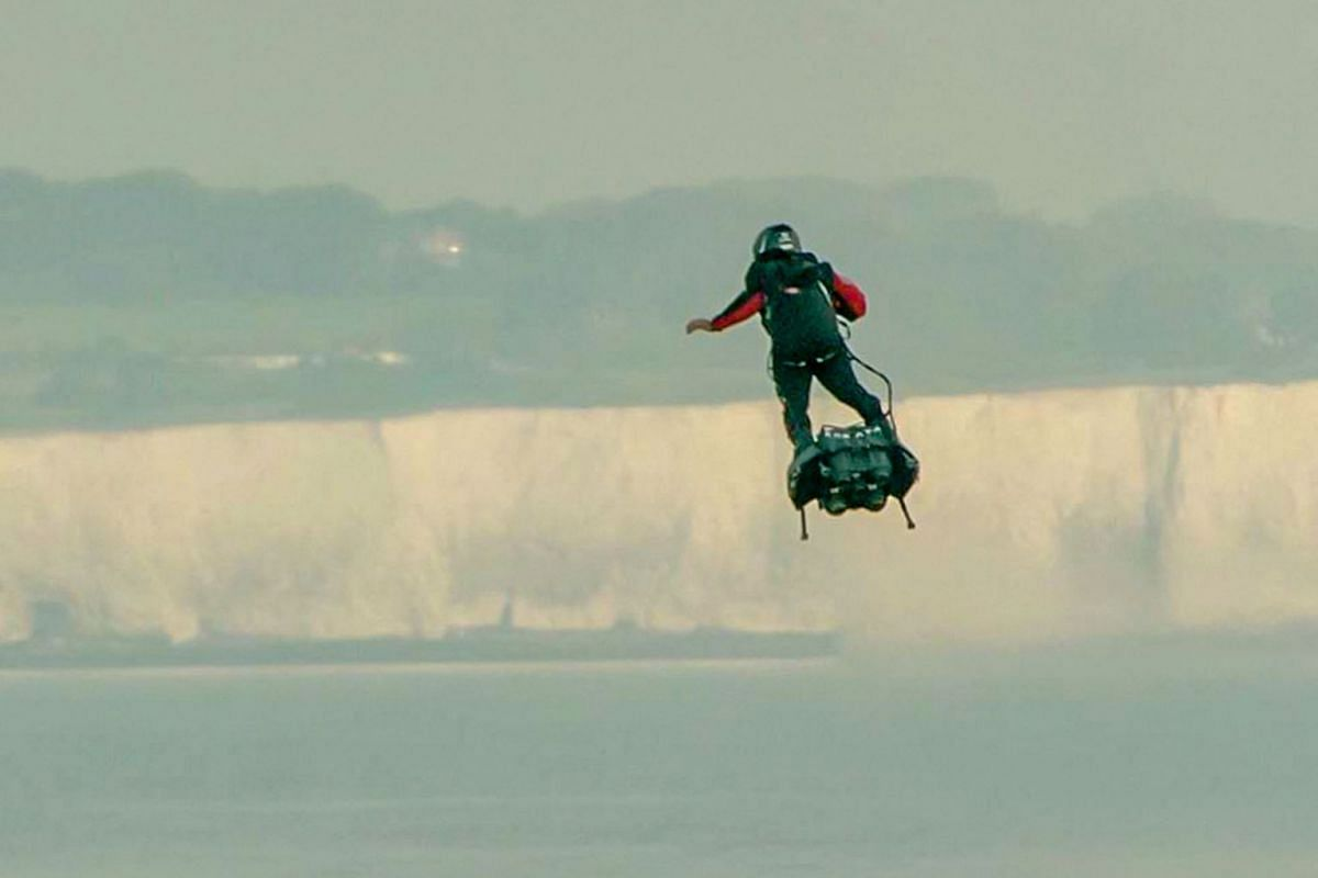 """In this screen grab from a handout video taken and released by Etoile Noire on August 4, 2019, Franky Zapata stands on his jet-powered """"flyboard"""" as he arrives at St. Margaret's Bay in Dover, during his attempt to fly across the 35-kilometre (22-mile"""