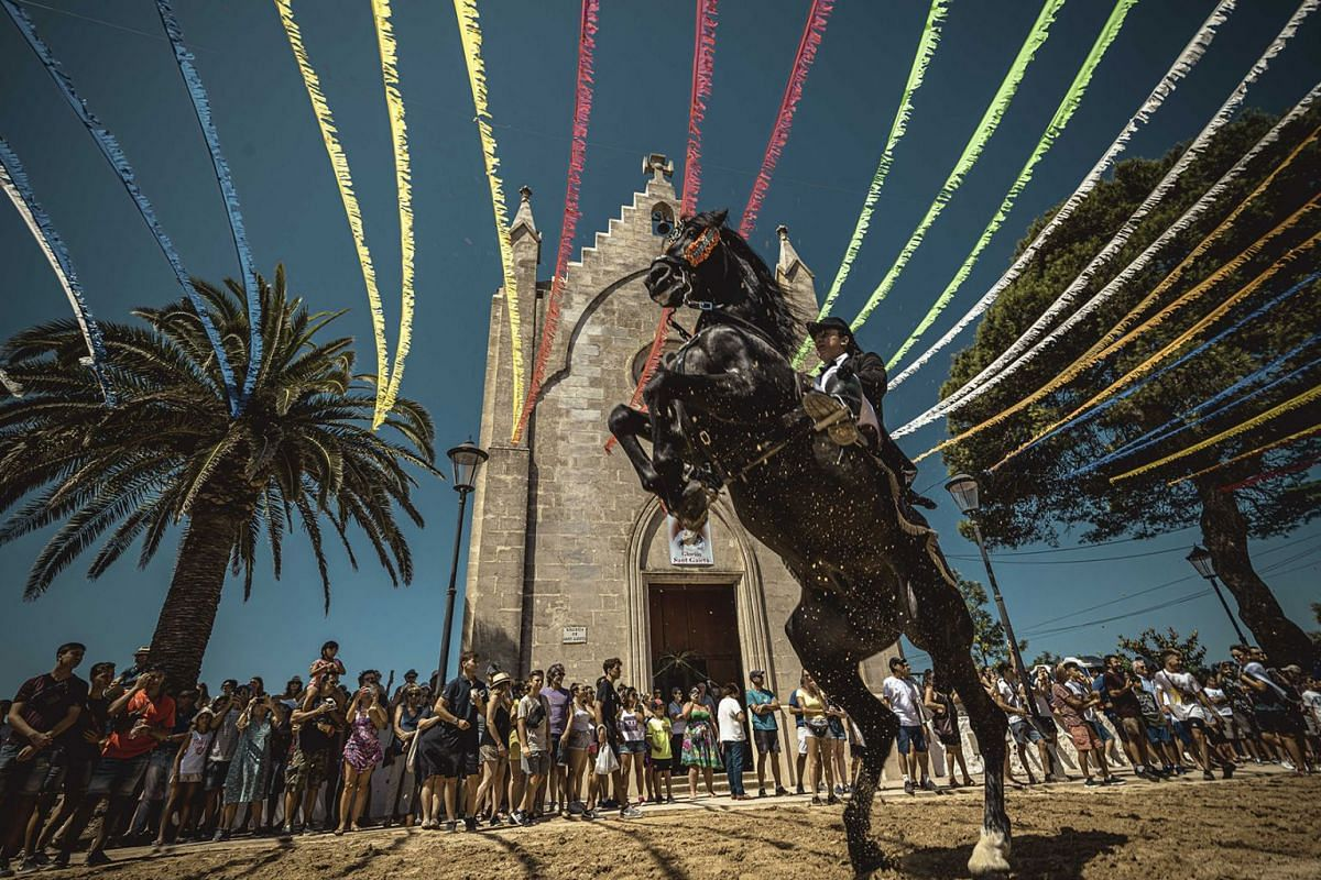 A horse rider rears up on his horse surrounded by a cheering crowd during the traditional 'Jaleo' at the Sant Gaieta Festival on August 4, 2019, in Llucmacanes,  Spain. PHOTO: ZUMA WIRE VIA DPA