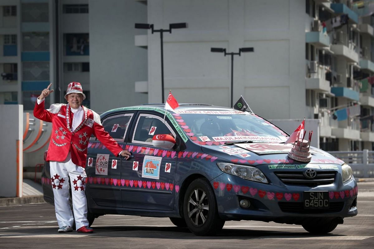 A photo issued on August 5, 2019, shows Gojek driver Henry Ho, who has been decorating his car and customising outfits for Singapore's National Day for more than 10 years, on August 1, 2019, at a multistorey carpark. PHOTO: THE STRAITS TIMES/GIN TAY