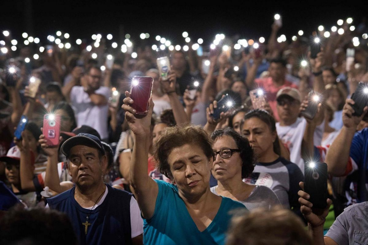 People hold up their phones, with the torch function turned on, during a prayer vigil organised by El Paso city, after a mass shooting left 20 people dead at the Cielo Vista Mall Walmart on Aug 4, 2019.