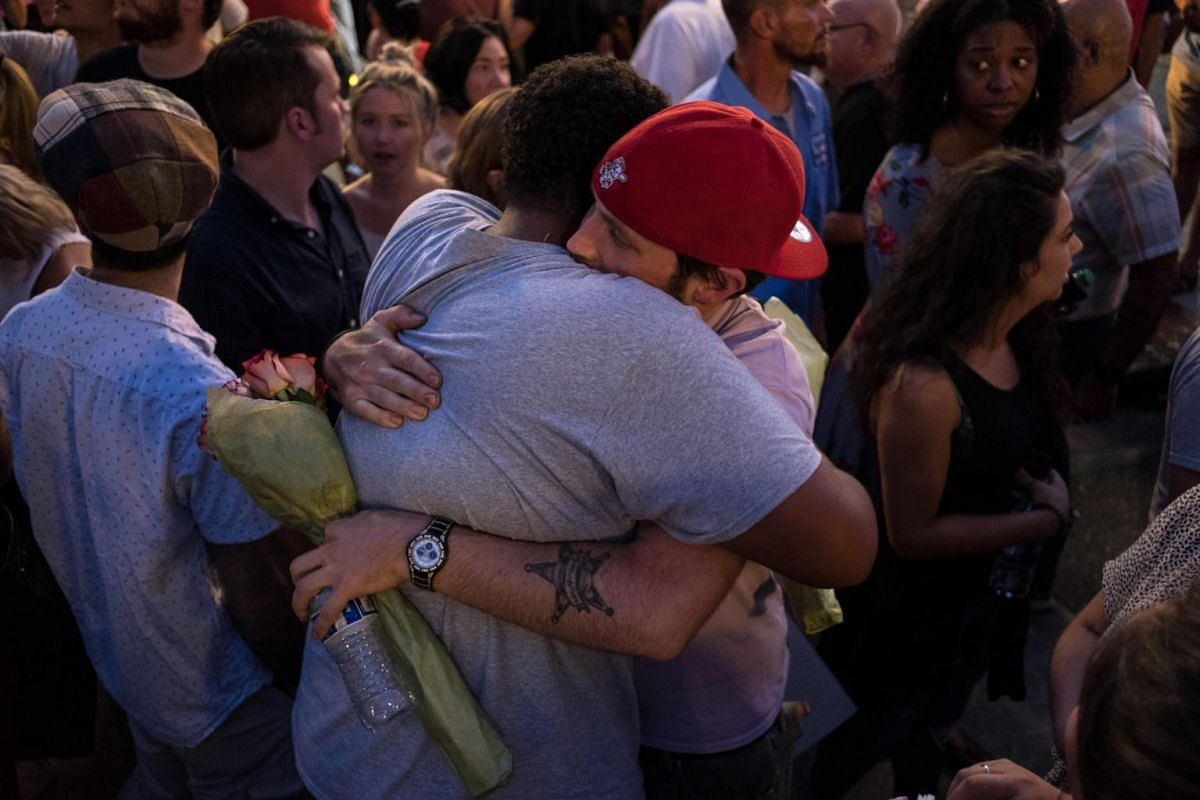 People comforting each other as they take part in a candle-lit vigil in honour of those who lost their lives or were wounded in a shooting in Dayton, Ohio.