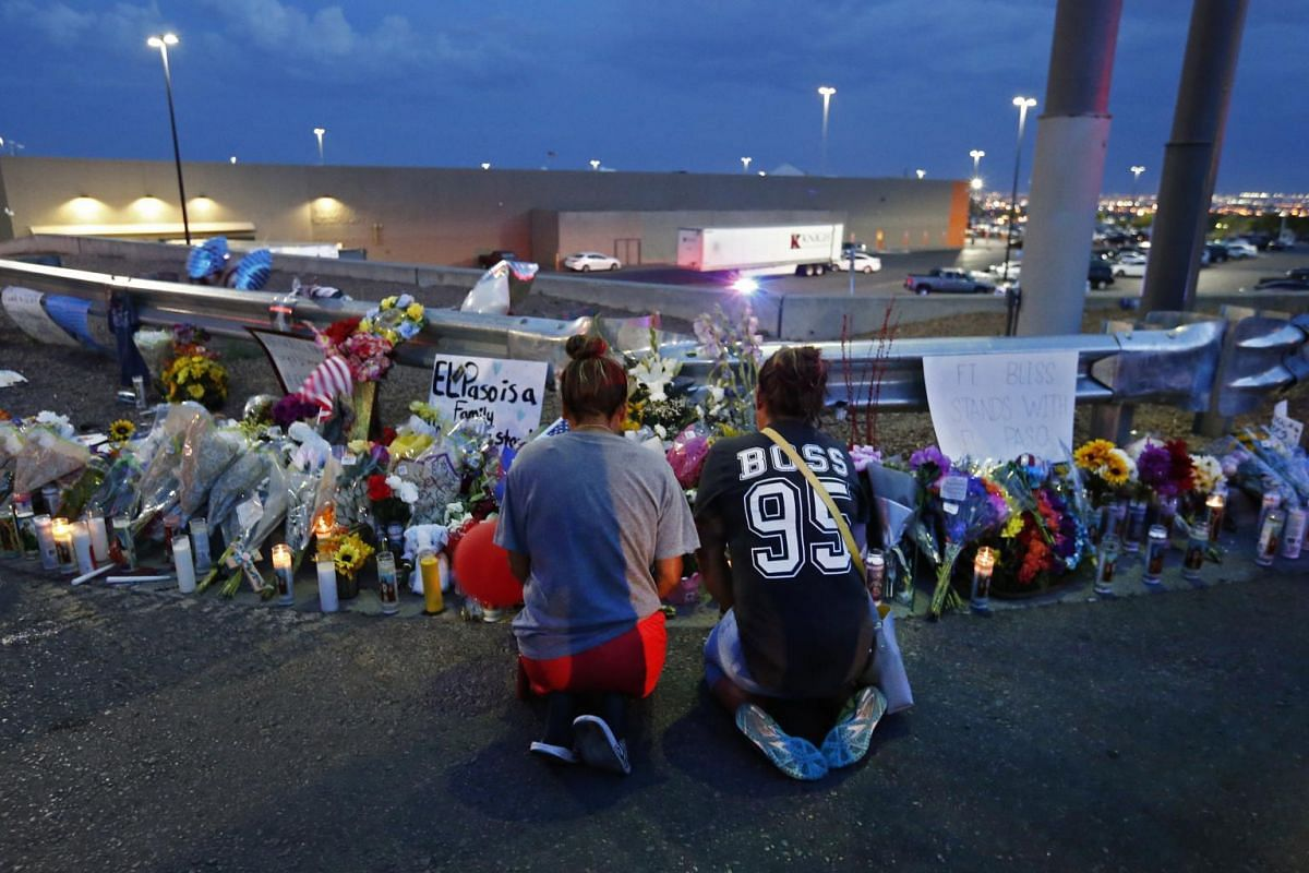 Two women kneeling at a makeshift memorial at the site of a mass shooting at a Walmart store in El Paso, Texas, on Aug 4, 2019.