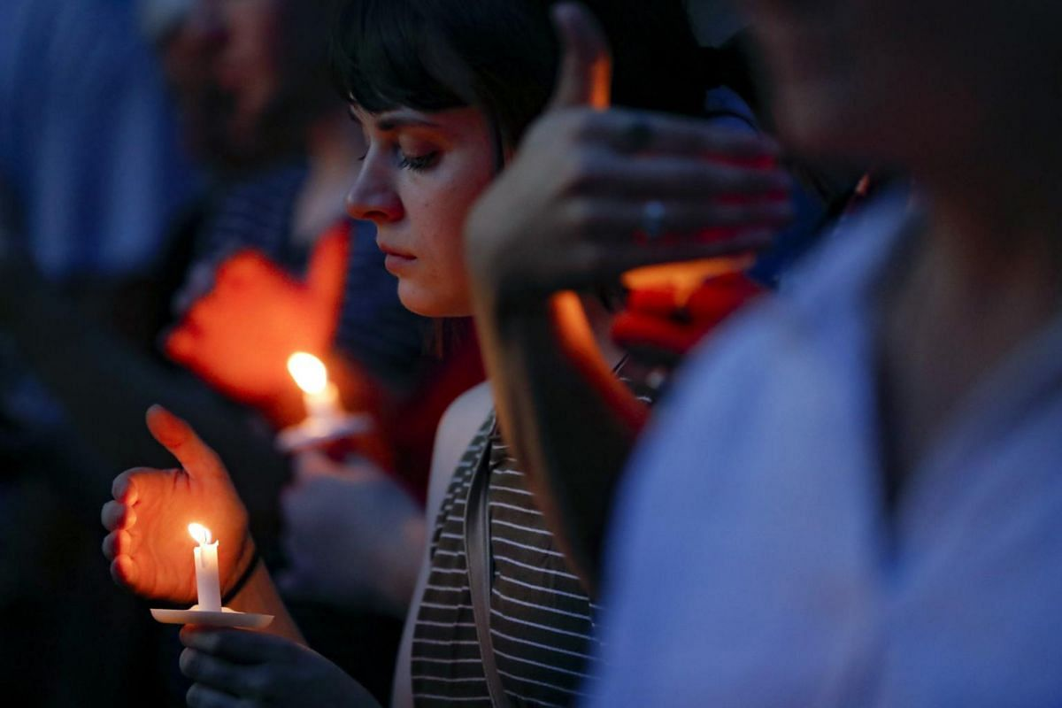Mourners bow their heads in prayer at a vigil held at the scene of a mass shooting in Dayton, Ohio.
