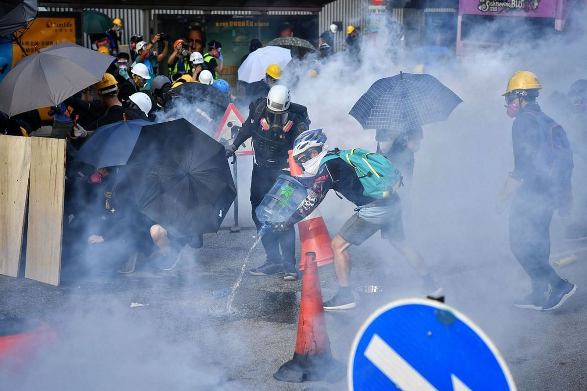 Protesters rushing to put out tear gas with water during a clash with the police outside the Legislative Council building, Aug 5, 2019.  PHOTO: CHONG JUN LIANG