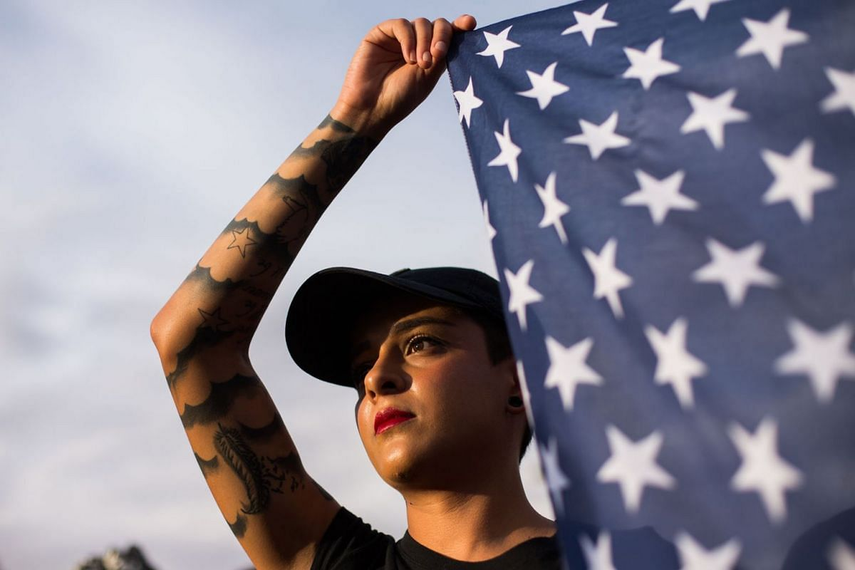 Jessica Torres holds an American flag during an interfaith vigil for victims of the Walmart shooting at Ponder Park in El Paso, Texas, Aug 4, 2019. PHOTO: THE NEW YORK TIMES