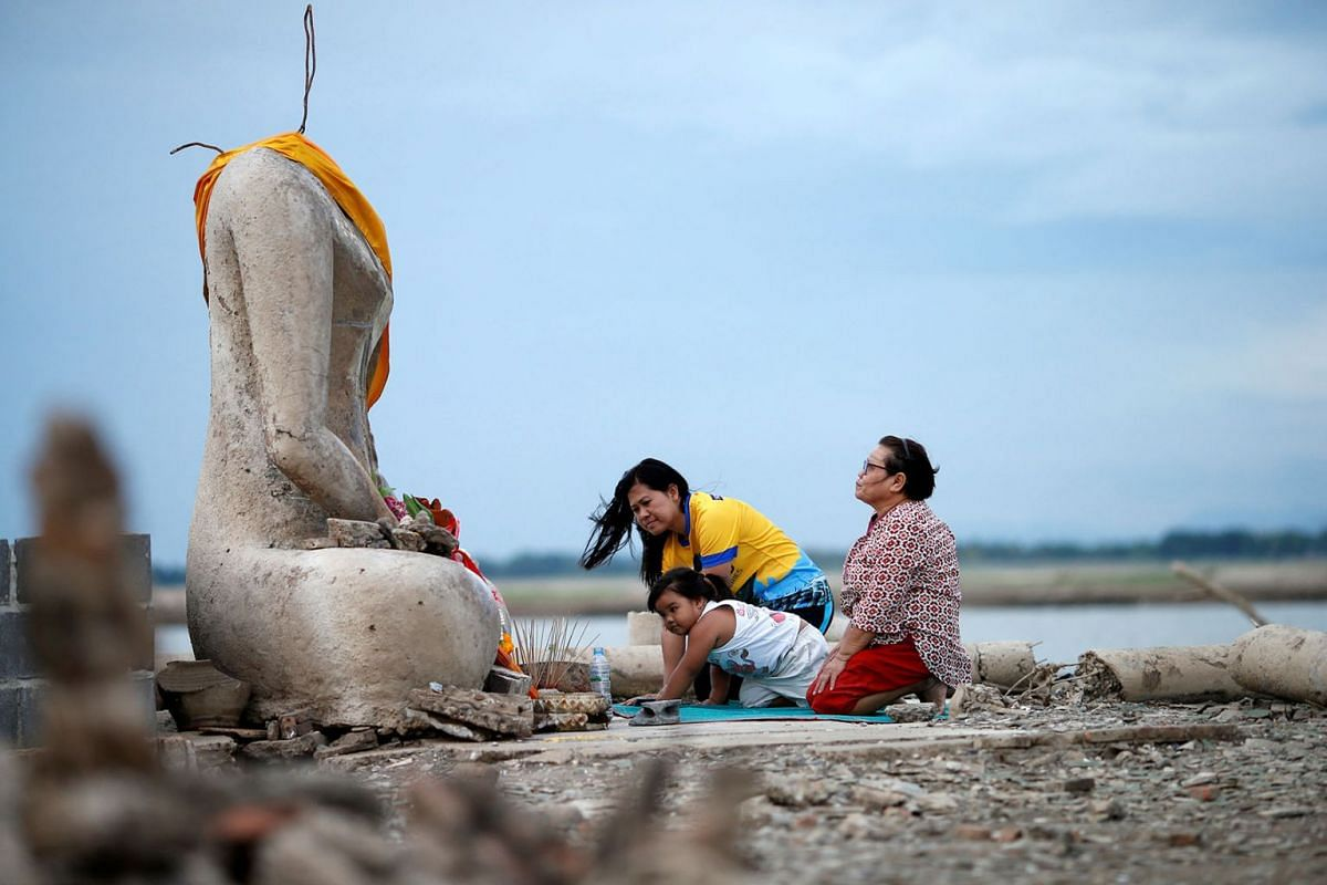 A photo issued on Aug 6, 2019, shows a family praying near the ruins of a headless Buddha statue, which has resurfaced in a dried-up dam due to drought, in Lopburi, Thailand, Aug 1, 2019. PHOTO: REUTERS