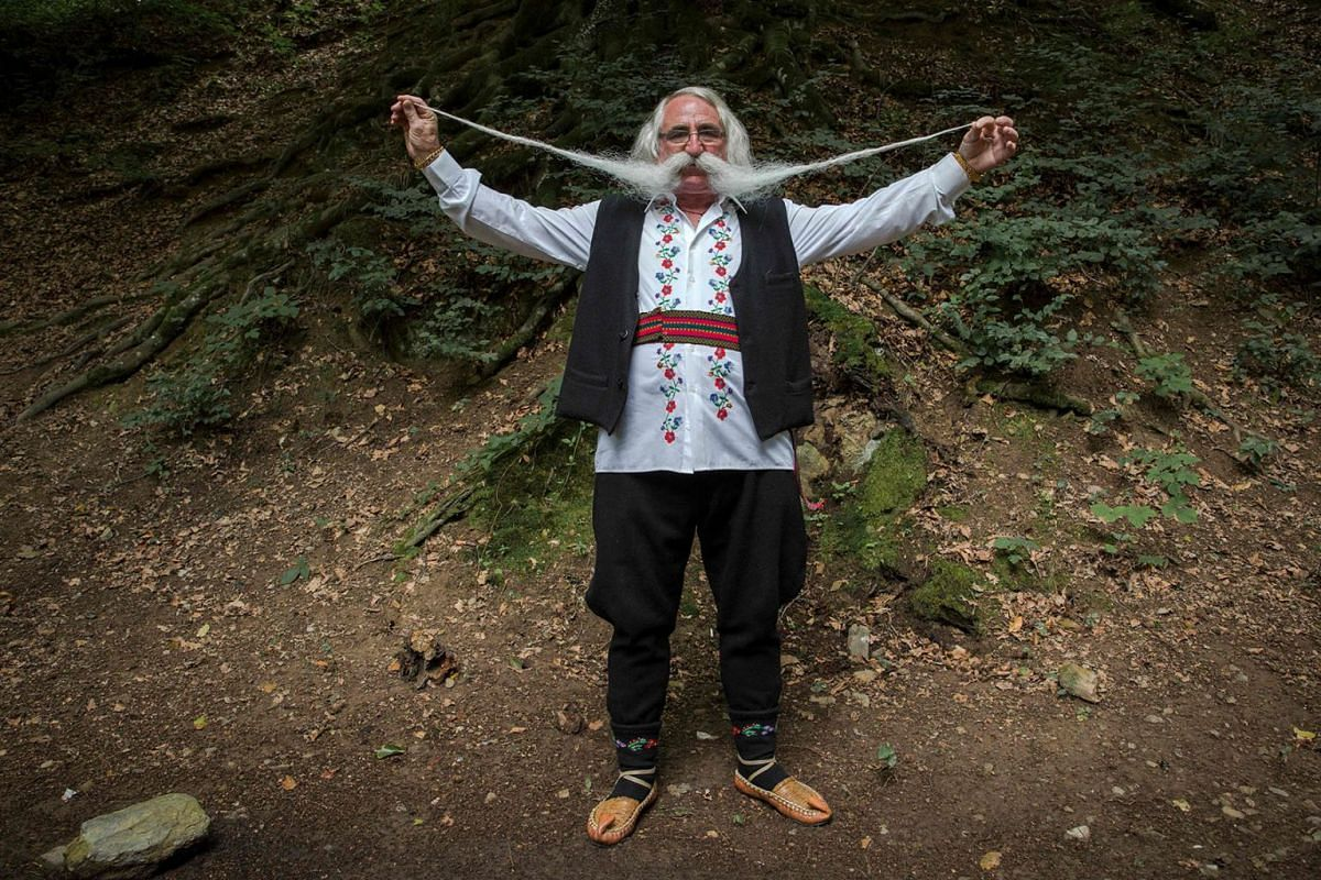 Zoran Lazarevic, 70-years-old, shows off his moustache as he takes part in the longest moustache competition at the 15th century Kalenic Serbian Orthodox monastery, near Rekovac, central Serbia on Aug 4, 2019. PHOTO: AFP