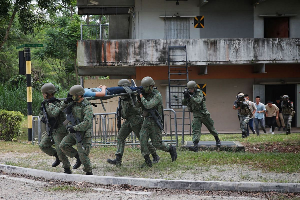 "Troops from Singapore and China evacuating ""civilians"" from the Murai Urban Training Facility, Aug 5, 2019. The raid marked the culmination of this year's 10-day Exercise Cooperation, in which about 120 soldiers from each side took part. PHOTO:"