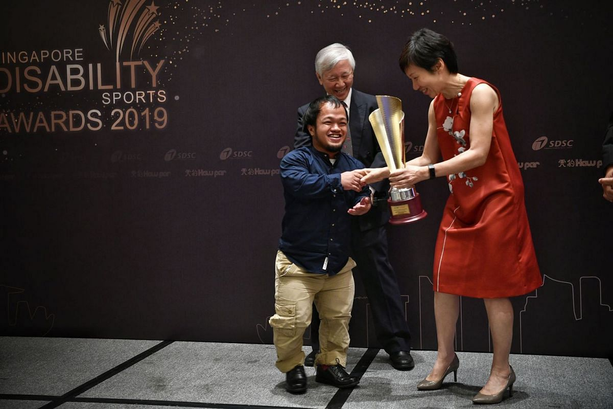 A jubilant Muhammad Diroy Noordin receiving his Sportsman of the Year trophy from Culture, Community and Youth Minister Grace Fu. Behind them is Haw Par Corporation executive director Han Ah Kuan. PHOTO: THE STRAITS TIMES/ARIFFIN JAMAR