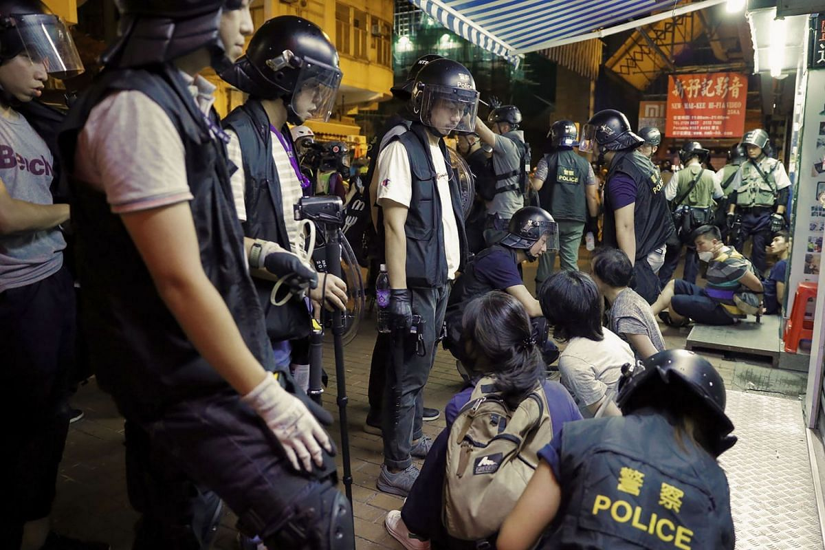 Arrested people are guarded by policemen during a face-off at Sham Shui Po district in Hong Kong, Aug. 7, 2019. PHOTO: AFP