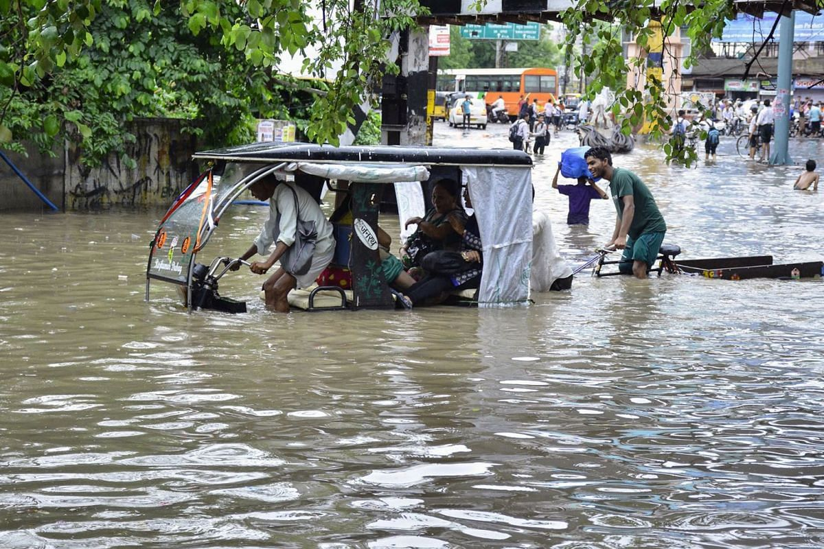 The driver of an electric auto rickshaw hovers over his seat after driving his passengers into a water-logged street following heavy rains in Mathura in Uttar Pradesh state on August 6, 2019. PHOTO: AFP