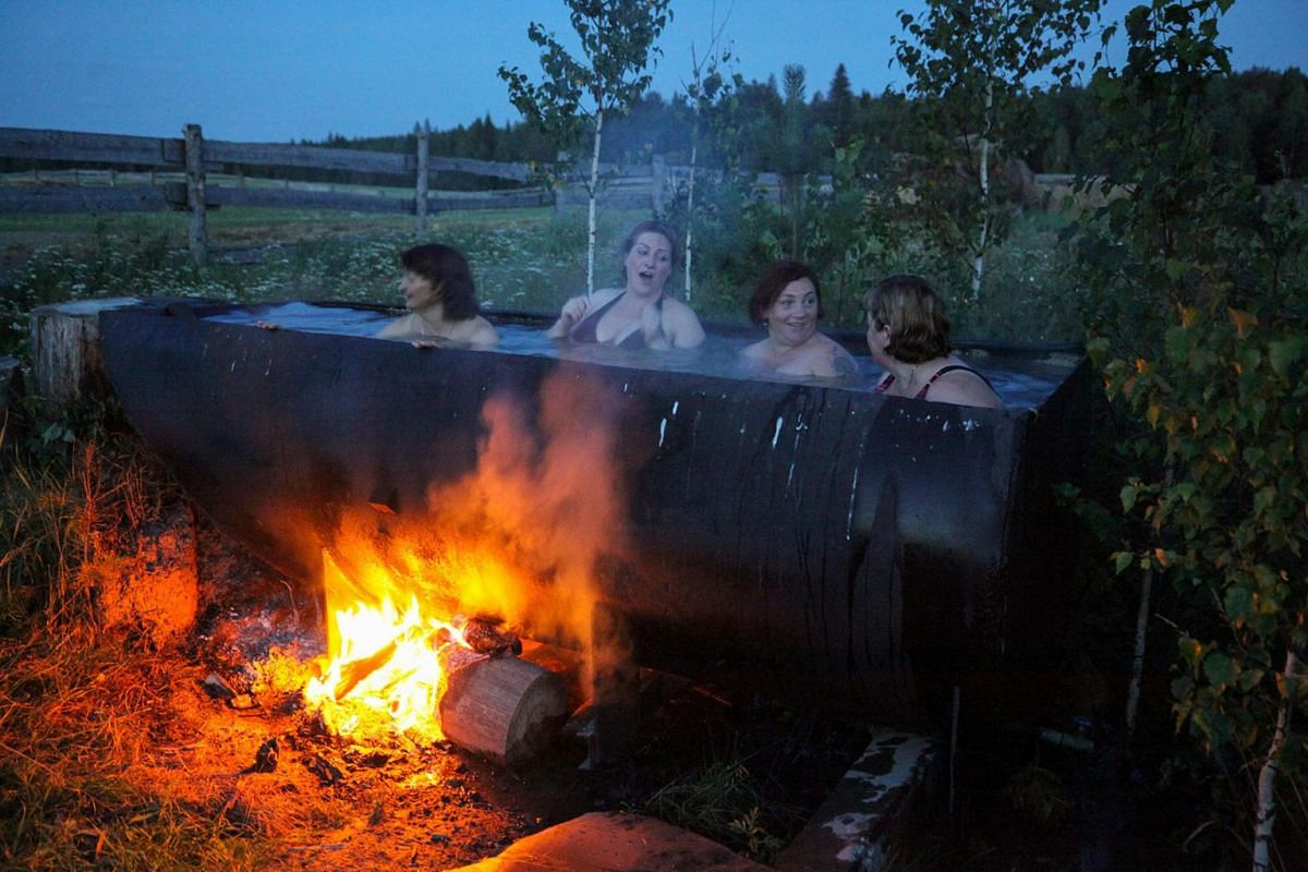 A photo issued on August 7, 2019 show Latvian women bathing in a huge tub heated by a bonfire in the village of Bobrovka, some 350 km of Omsk, on July 31, 2019. PHOTO: AFP