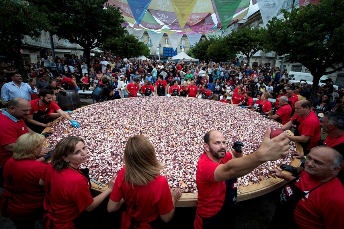 People prepare a giant octopus 'tapa' to try to break a new world record in O Carballino in Galicia, northern Spain, August 6, 2019, on occasion of the celebration of the traditional octopus day on 11 August. PHOTO: EPA-EFE